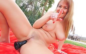 Horny GILF with natural boobs fucks herself outdoors