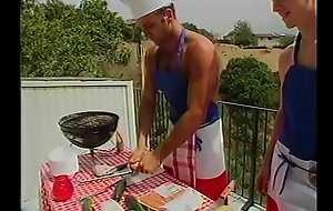 Young Gregg Clarke helps blond shit-hunter Paul Morgan to cook sausages and fish frames on barbeque grill